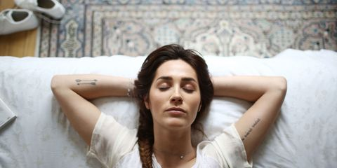 Young woman with tattoos lying in bed asleep
