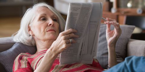 Older woman doing crossword puzzle at home on sofa