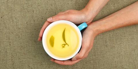 Cropped Hands Of Woman Holding Green Tea Cup