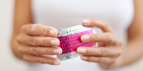Woman's hand holding birth control pills, cropped