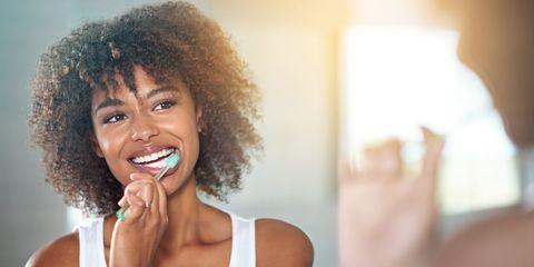 Femme, brossage, dents, regarder, salle bains, miroir