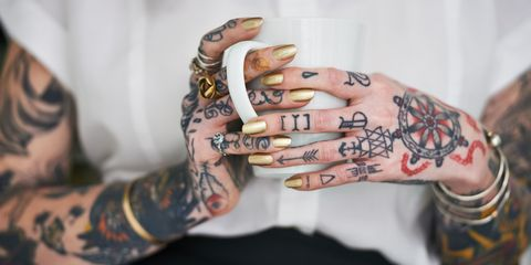 Woman with tattoos holding mug