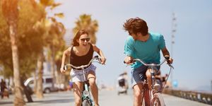 Couple biking in sun on holiday