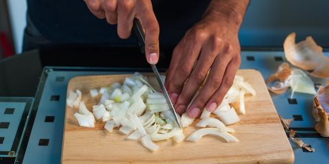Hands of a man chopping onions