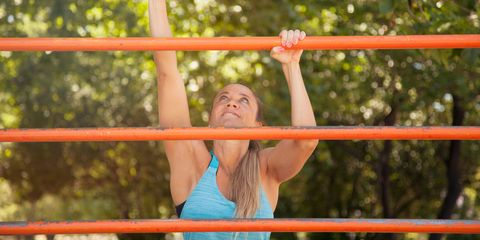 Woman Climbing Metallic Fence Against Trees At Park