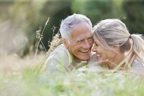 Happy elderly couple sitting in long grass