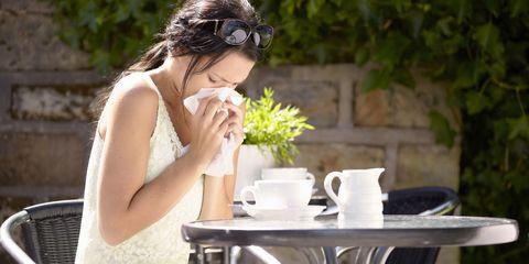 Woman sneezing outside cafe