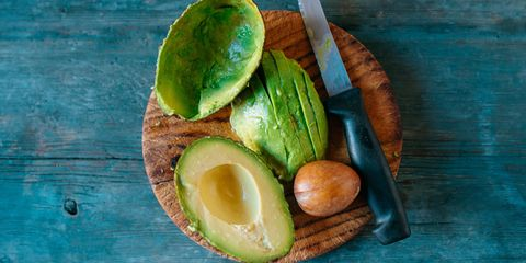 Sliced avocado, kernel and knife on wooden board