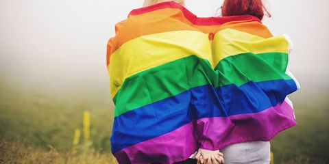 Two women holding hands covered in Pride rainbow flag