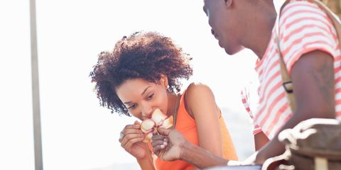 Young woman smelling flower giving to her by young man