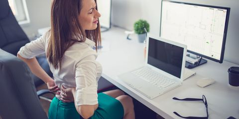Woman sat at desk in office with lower back pain