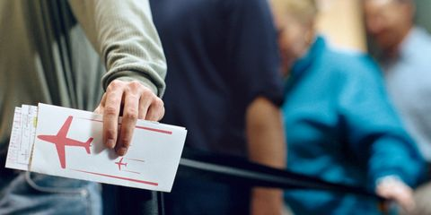 Man holding plane ticket in airport queue