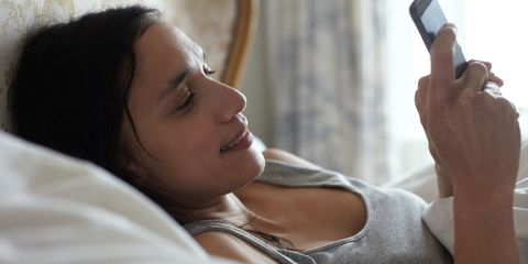 Woman using her phone in bed