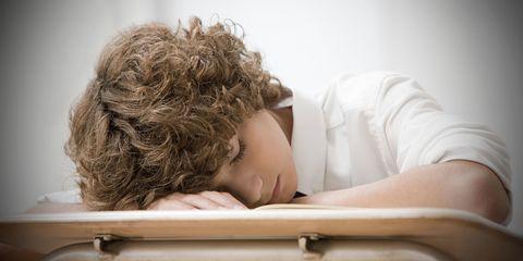 Secondary school boy asleep on desk