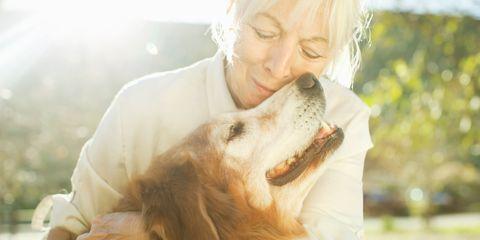 Woman and dog hugging smiling