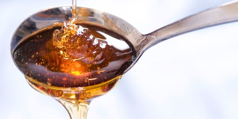 A drizzle of syrup or honey falls into and out of a spoon.