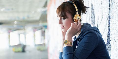 Woman listening to music on gold headphones