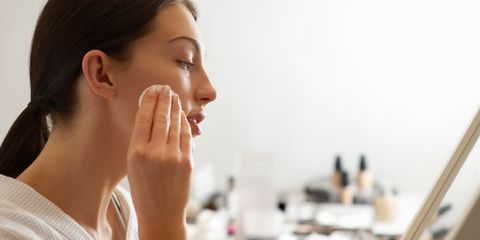 Woman with oily skin cleansing face