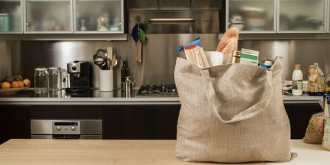 A resusable, cloth grocery bag full of milk, wine, bread on a kitchen counter.