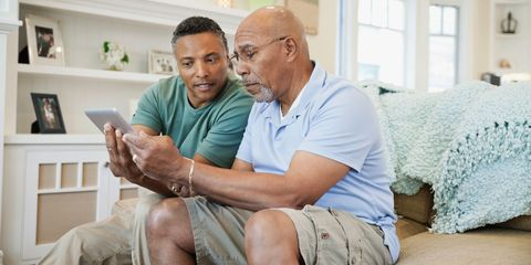 Son helping senior father to use digital tablet