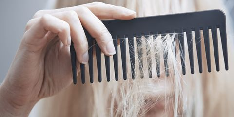 Woman combing dry and damaged hair