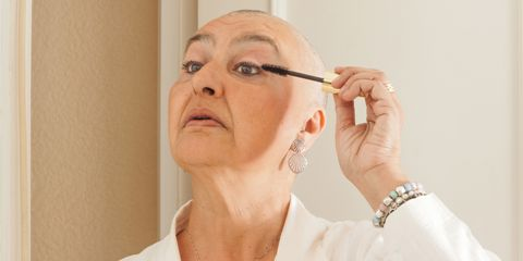 Fighting against breast cancer. A mature woman in her bathroom, in pajamas, in front of the mirror, getting ready to make up.