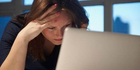 Stressed businesswoman using laptop in office