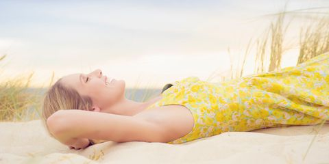 Woman lying in sand smiling