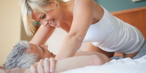 A woman on top of her partner smiling and pinning his arms down