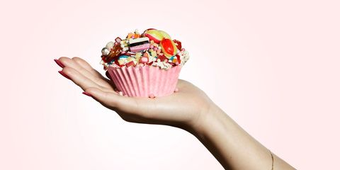 Woman holding cupcake in front of pink backdrop