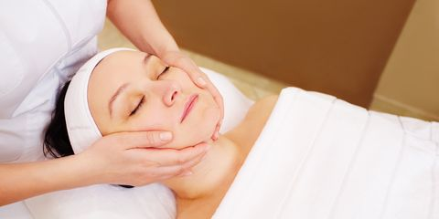 High Angle View Of Woman Receiving Facial Massage In Spa
