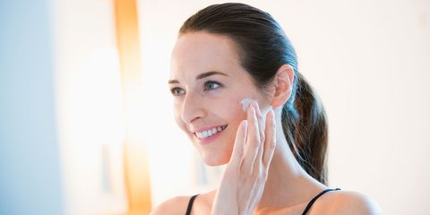 Smiling woman applying face cream to cheek