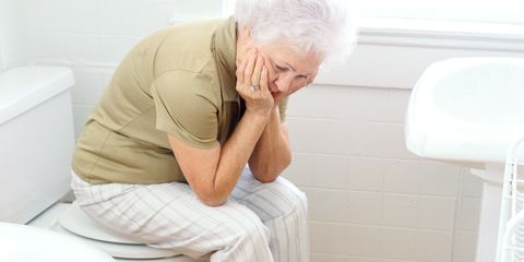 portrait of an elderly woman sitting on a closed commode looking down