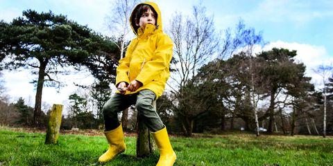 Boy in yellow anorak sitting on park fencepost