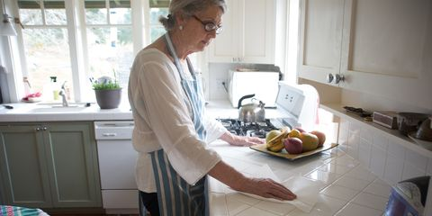 Woman cleans tiled countertop in kitchen