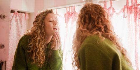 Girl checking skin in mirror
