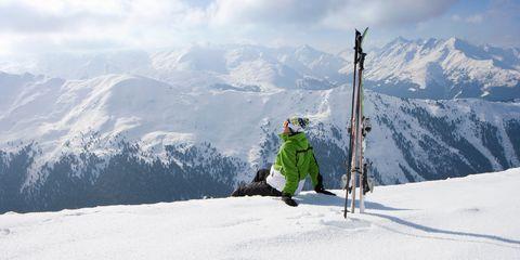 Man sitting on mountain with skis
