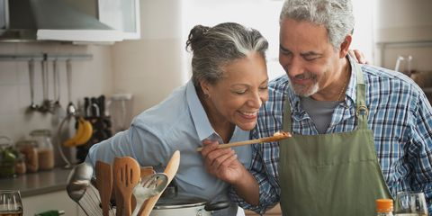 Senior couple cooking in kitchen happy