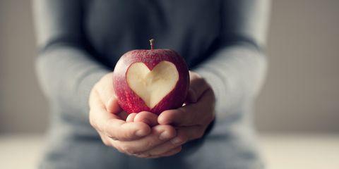 Hands holding heart apple
