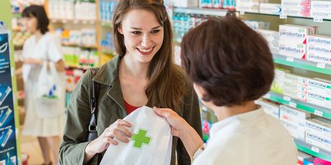Pharmacist handing over prescription to young woman