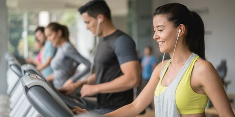 Woman in gym on treadmill smiling