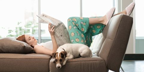 Woman relaxing reading paper at home on sofa with dog