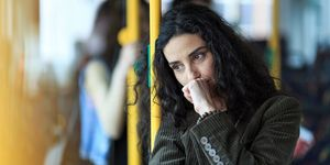 Woman looking stressed on the tube or bus