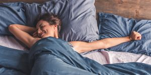 Happy woman in bed smiling and stretching