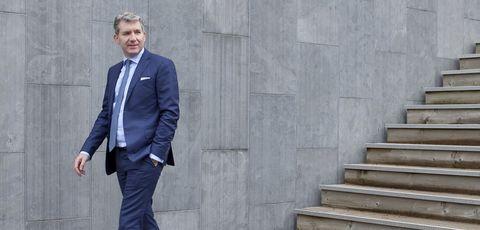 Suit, Standing, Formal wear, Blazer, White-collar worker, Outerwear, Tuxedo, Businessperson, Electric blue, Jacket,