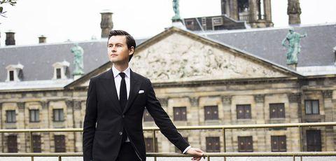 Suit, Formal wear, White-collar worker, Standing, Tuxedo, Businessperson, Outerwear, Blazer, Style, Gesture,