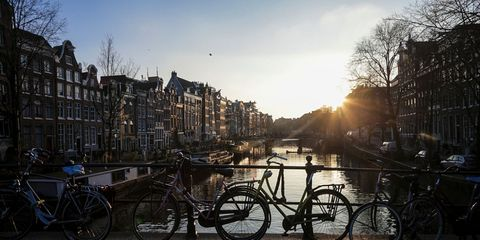 Bicycle, Waterway, Canal, Sky, Bicycle wheel, Mode of transport, Morning, Vehicle, Urban area, Bicycle accessory,