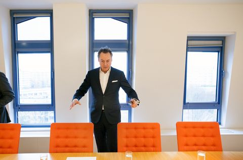 Orange, Suit, Businessperson, Job, Window, Formal wear, Furniture, Interior design, Daylighting, White-collar worker,