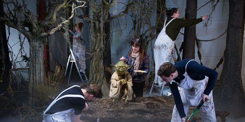 "An artist works on a wax sculpture of Yoda from ""Star Wars."""