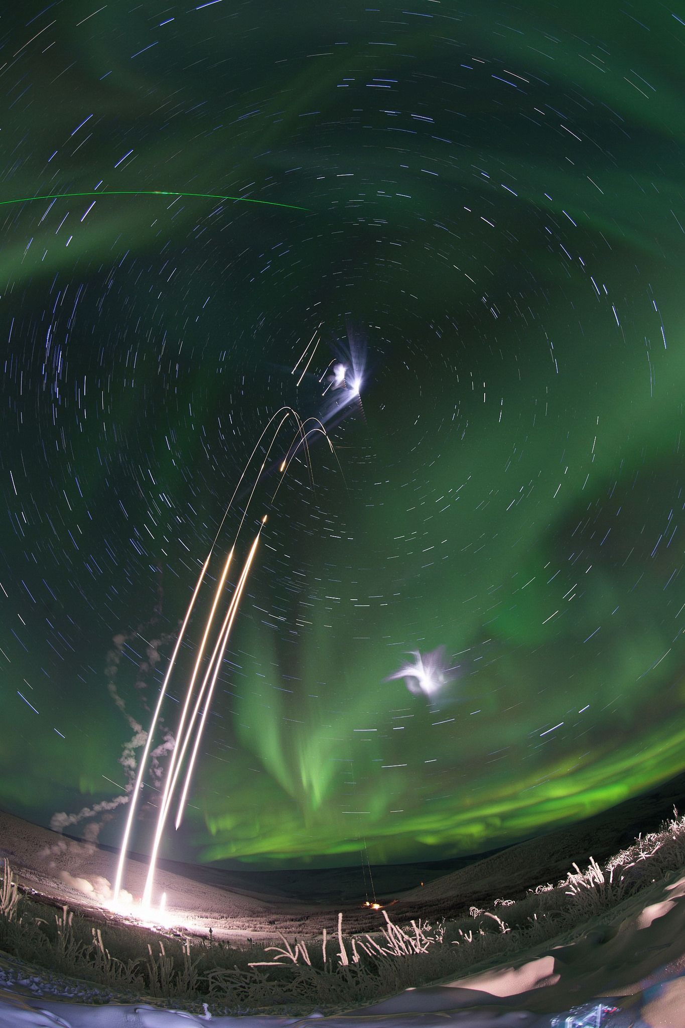 A composite image of four rocket launches in Alaska of the M-TeX and MIST Experiments. Many stars are visible in the background.